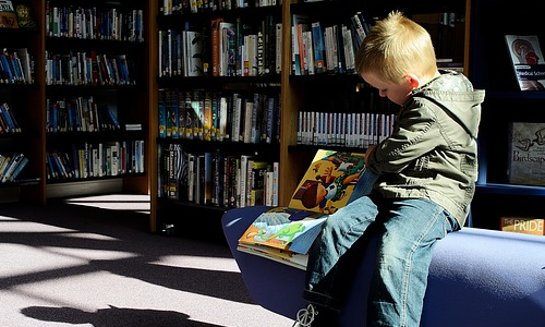 boy in a library reading